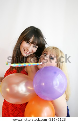 two young pretty woman in birthday cap with noisemaker