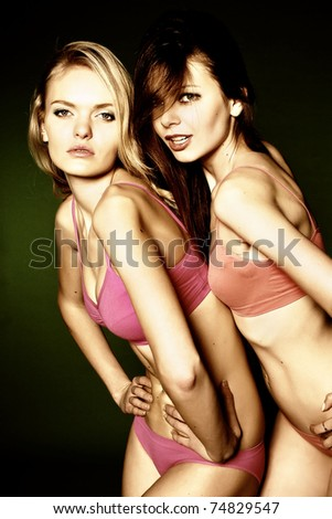 Two young pretty woman in colorful bikinis - stock photo
