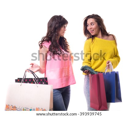two young pretty woman standing isolated on white background paper shopping bags from the store. girlfriend shows off a new dress - stock photo