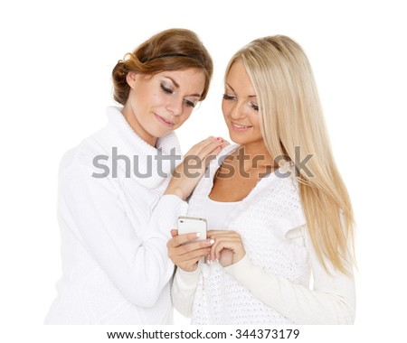 Two young pretty women in winter clothes with a mobile phone on a white background. - stock photo