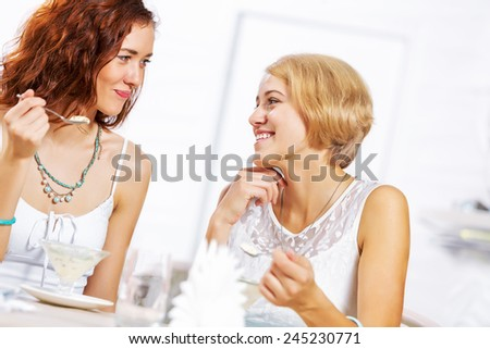 Two young pretty women sitting at cafe and eating dessert