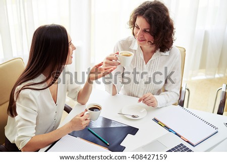 Two young pretty women talking about something and hold coffee in hand in the spacious office - stock photo