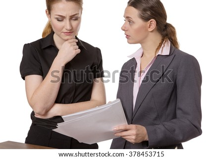 Two Young Professional Businesswomen Discussing Paperwork In The Office
