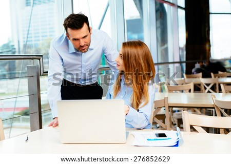 Two young professionals planning work in front of a laptop - stock photo