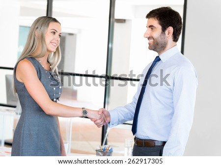 Two young professionals shaking hands  - stock photo