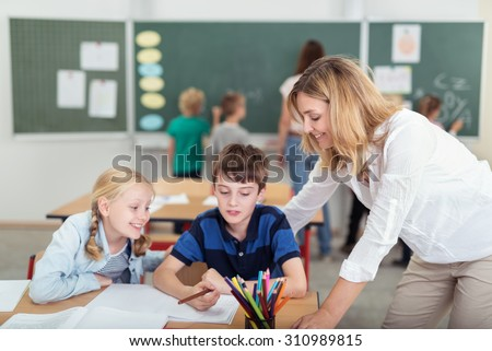 Two young pupils in class with their attractive female teacher working together on the class notes of a young boy - stock photo