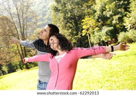 Two young relaxed people in nature with opened arms looking up and breathing fresh air - stock photo