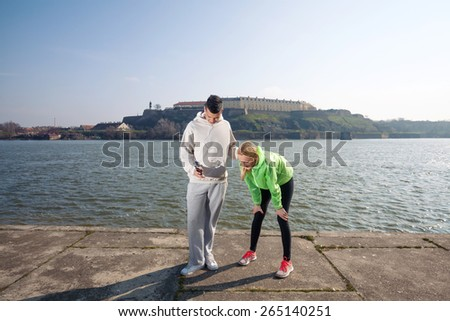 Two young runners taking a break while jogging by the river - stock photo