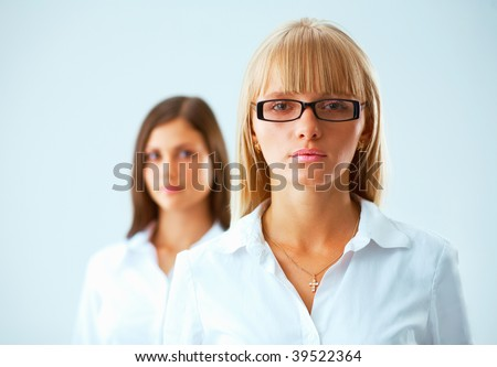 Two young  serious business women on light blue background with a fair hair woman in focus - stock photo