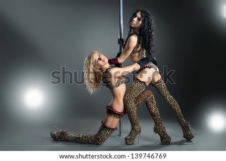 Two young sexy women exercise pole dance against a dark background - stock photo