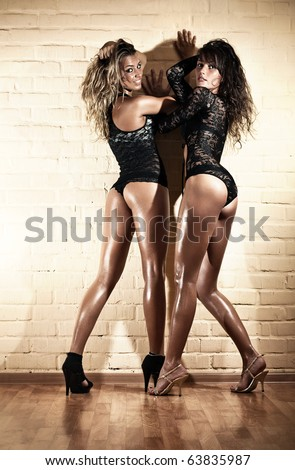 Two young sexy women. On wall background. - stock photo