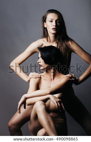 two young sexy women or girls with stylish short and long brunette hair and pretty face with naked or bare body on grey background