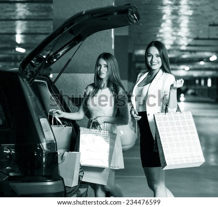 Two young shoppers on a car parking - stock photo