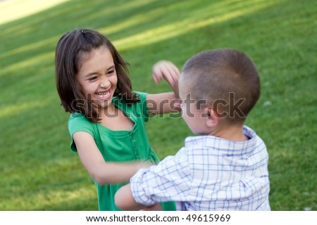 Two young siblings playfully hitting each other and rough housing.  Slight motion blur with sharp focus on the girls face. - stock photo