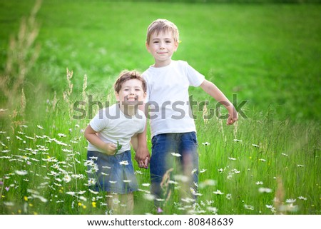Two young siblings playing in green field.