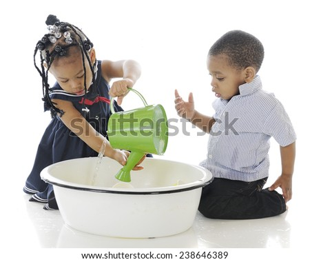 Two young siblings playing with a watering can in a tub of water.  On a white background. - stock photo