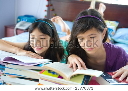 Two young sisters enjoying their reading in home environment