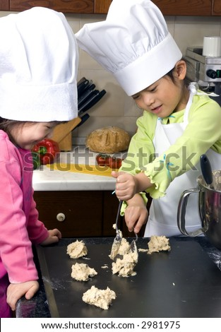 Two young sisters have fun in the kitchen making a mess....I mean making cookies. Education, learning, cooking, childhood - stock photo