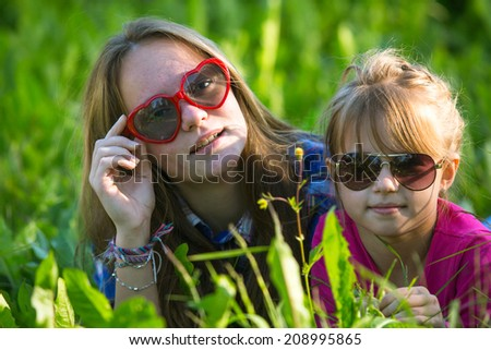 Two young sisters lying in the grass, sun-glasses. - stock photo