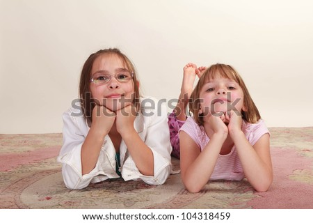 Two young sisters lying on a carpet with hands on chin - stock photo