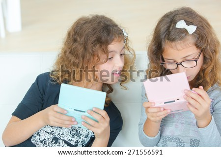 Two young sisters playing video gales - stock photo
