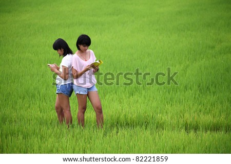 Two young sisters reading a book in paddy field