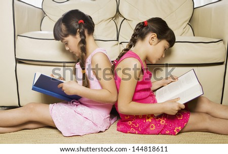 Two young sisters reading back to back