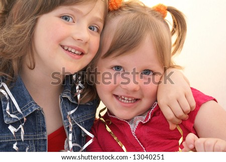 Two young sisters sit embraced each other, their faces get happiness.