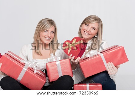 Two young sisters surrounded by gift boxes, some of them heart shaped - stock photo