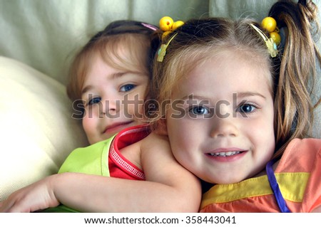 Two young sisters tussle on the couch in their home.  They are both smiling and happy.  They both have pigtails. - stock photo