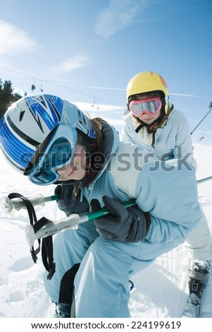 Two young skiers bending over, smiling at camera - stock photo