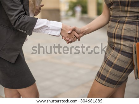 two young slim business women shaking hands in street No face Unrecognizable person Handshake between Businesswoman outside against modern building and stones floor  - stock photo