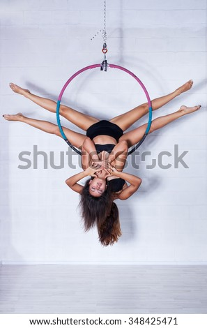 Two young slim sports women hanging on ring upside down in bright white interior - stock photo