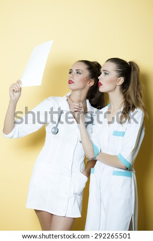 Two young smart serious sexy attractive doctor and nurse in white medical uniform with stethoscope on neck looking in sheet of paper with clinical record standing on yellow background copyspace - stock photo
