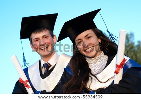 Two young smiley graduate students in cloak and diploma sitting outdoors at sunset light - stock photo