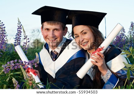 Two young smiley graduate students in gown and diploma sitting outdoors at sunset light - stock photo