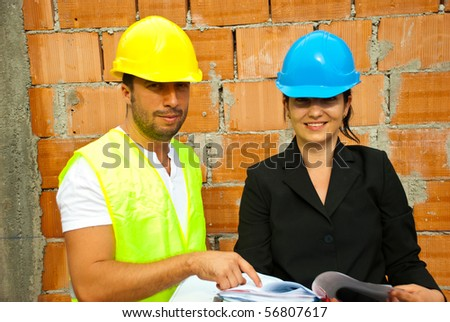 Two young smiling architects with plans  working on site and holding plans,man pointing to paper - stock photo