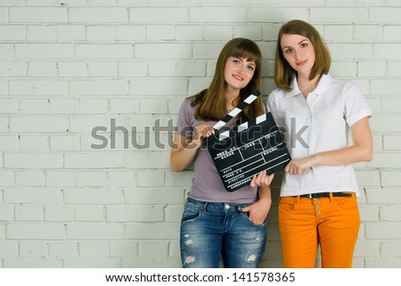 Two young smiling attractive girls holding a clapboard - stock photo
