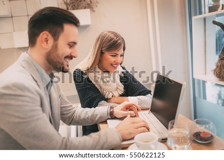 Two young smiling businesspeople working on laptop on a break at cafe. Selective focus.