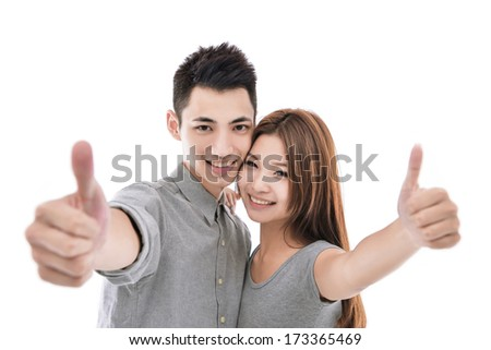 Two young smiling people with thumbs-up gesture - stock photo