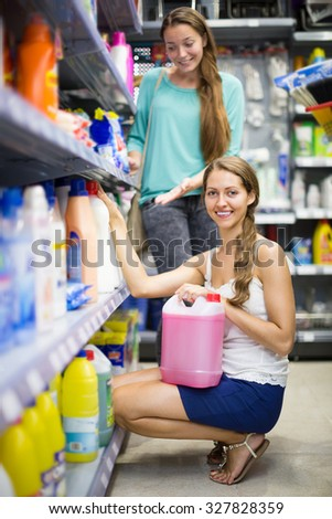 Two young smiling women selecting detergents at the household store