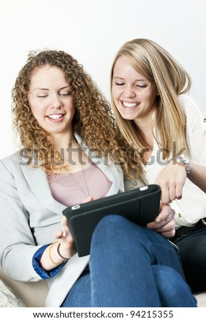Two young smiling women using tablet computer at home
