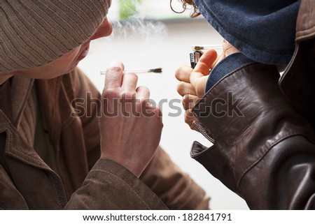 Two young smokers dressed in jackets smoking joints - stock photo