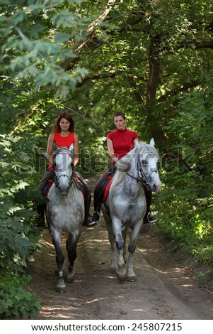 Two young sportswoman are riding along a forest road in summer - stock photo