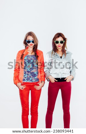 Two young sporty girl friends in sunglasses standing together.  indoor portrait. White background not isolated - stock photo
