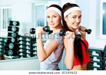 Two young sporty woman in the gym centre. - stock photo