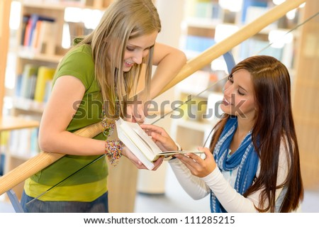 Two young student girls on high school library stairs - stock photo