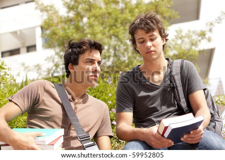 two young student reading books at the school (selective focus) - stock photo