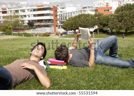 two young students sleeping at the grass over books and a soccer ball - stock photo