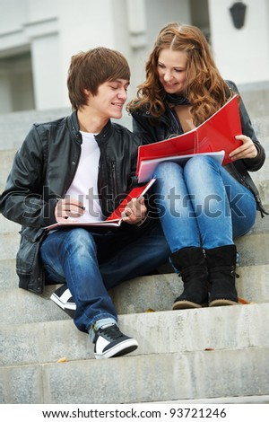 Two young students studying with worksheets and notebooks outdoors - stock photo